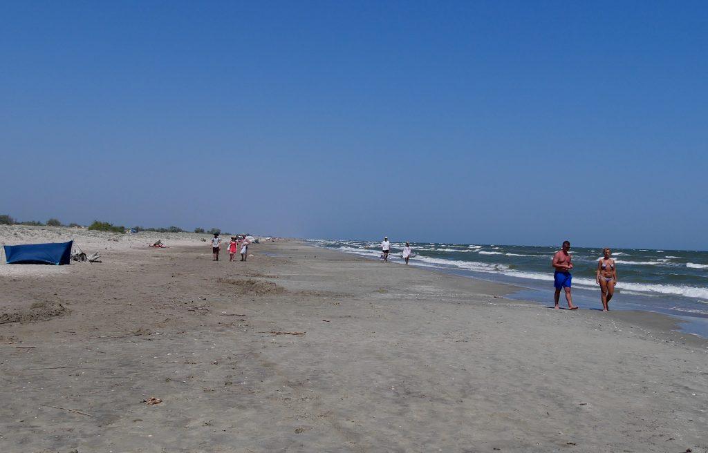oameni care merg pe plaja din Sfântu Gheorghe