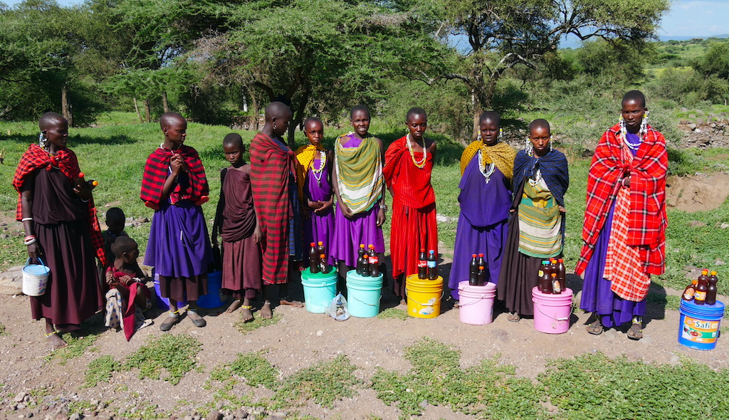 Femei și copii masai stau aliniați și pozează