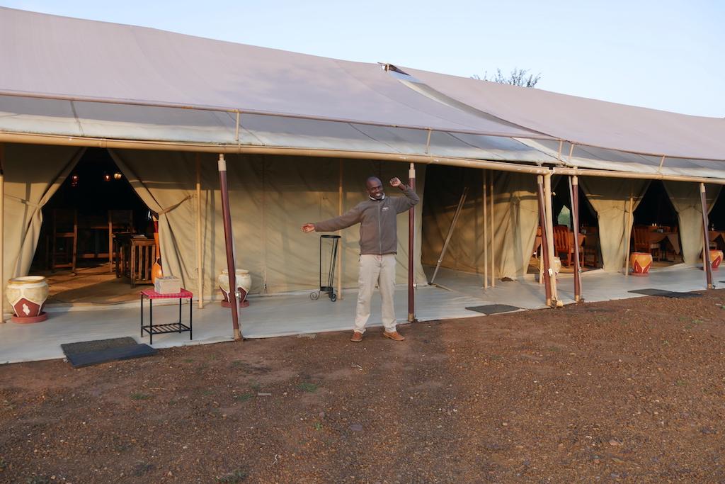 Un om își întinde brațele în fața unor corturi